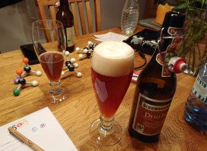 Zwei Biergläser und Flaschen auf einem Tisch, zusammen mit Audio-Equipment und Molekülmodellen auf einem Tisch
