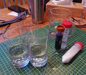 Gläser mit Wasser, ein Probenröhrchen mit brauner Kappe, zwei Probenröhrchen mit roter Kappe