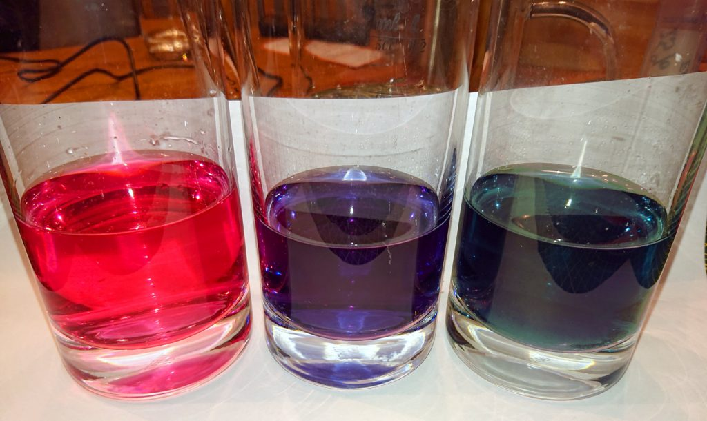 Rotkolhsaft in Wasser, drei Gläser, links mit Essig rosa, mit pures Wasser, blau, rechts mit Natron, grün